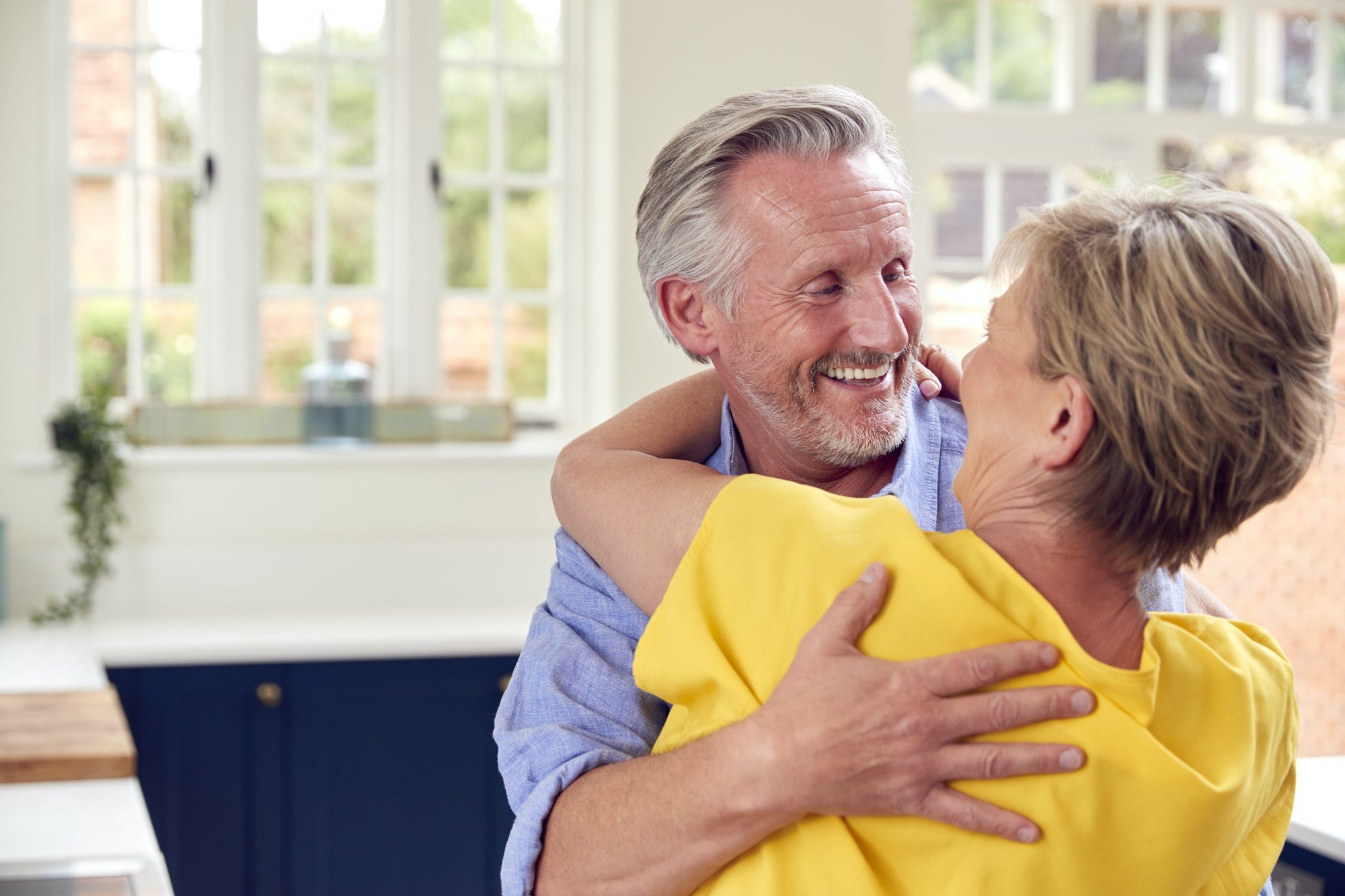 Loving Retired Couple Hugging In Kitchen At Home Together