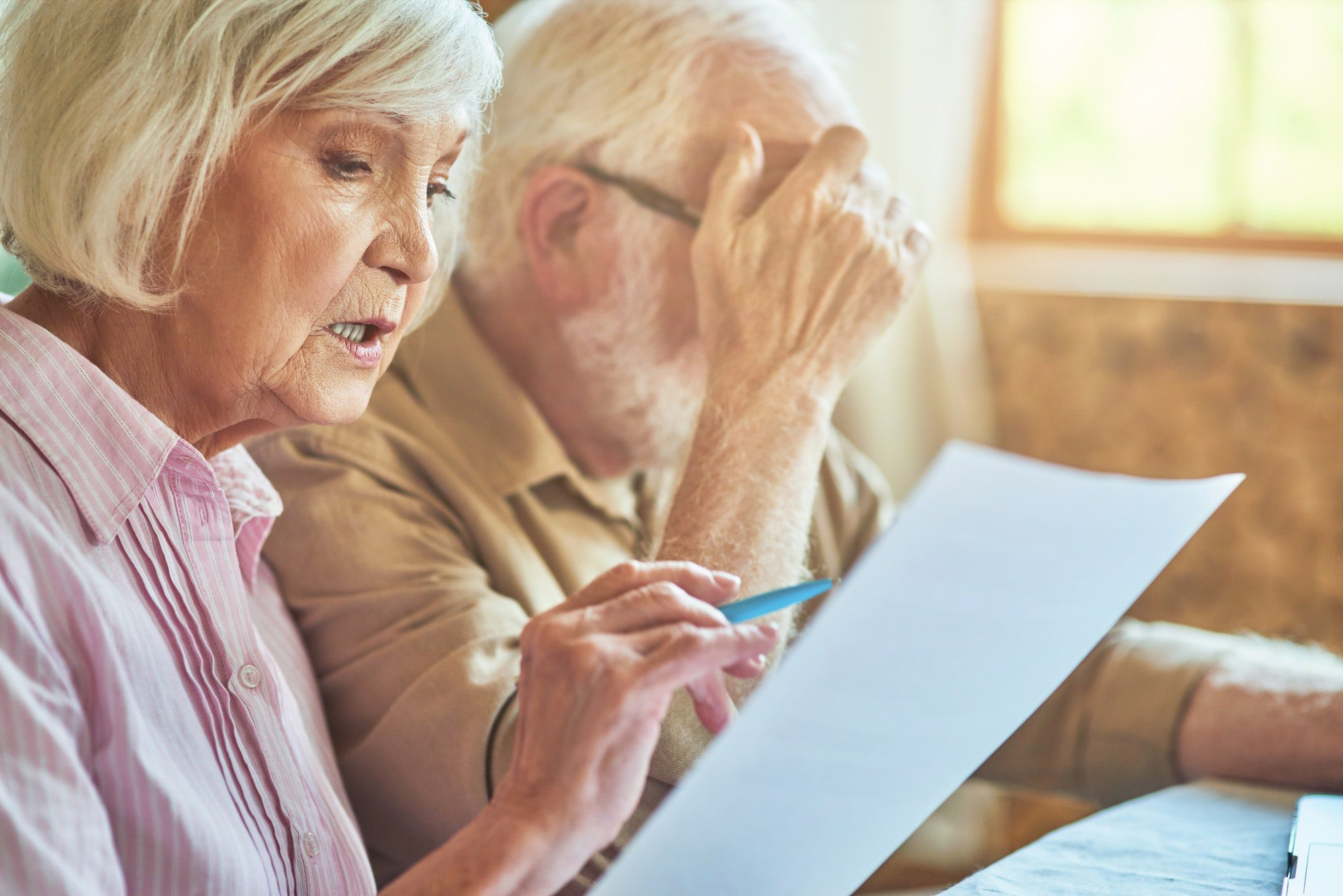 Senior husband and wife analyzing finance papers at home